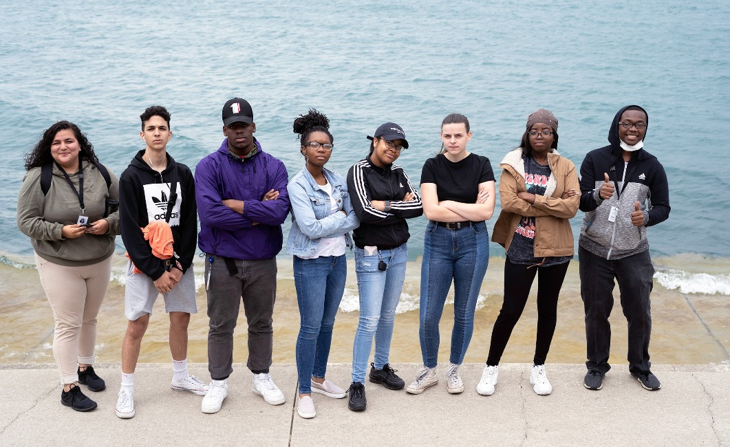 Teen members of the Adler Planetarium's Youth Leadership Council pose for a group photo in front of Lake Michigan.