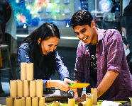 A couple smiles while working on a task together in one of the Adler's Community Design Labs.