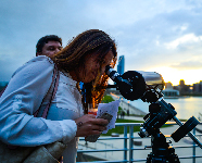 A guest peers out of a telescope on the Adler's terrace.