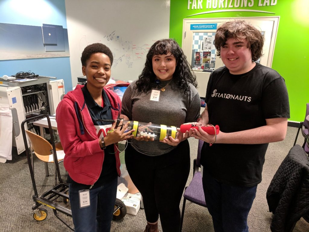 From left, Adler teens Carmen Jones, Giovanna Rossi, and Jack Morgan show off an important piece of technology they all helped create. Listen to the Aquarius Project Podcast to find out what it is!