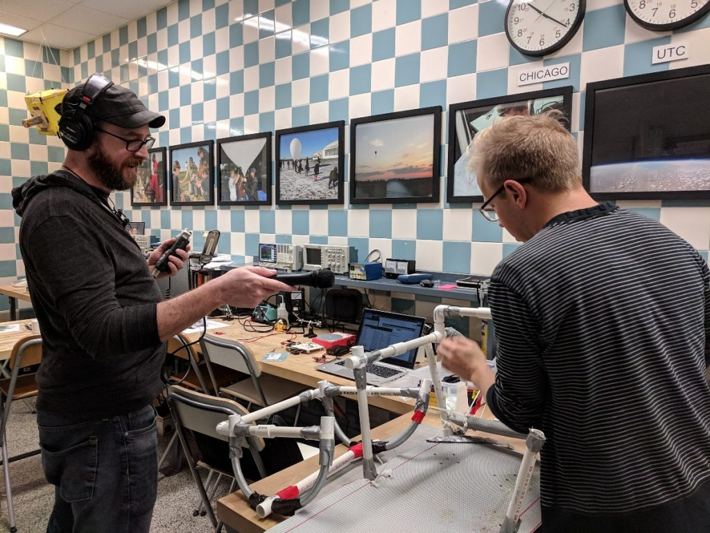 Project leader Chris Bresky (right) tries to reassemble a sled prototype from 2017 while podcast producer Erin Kahoa records.