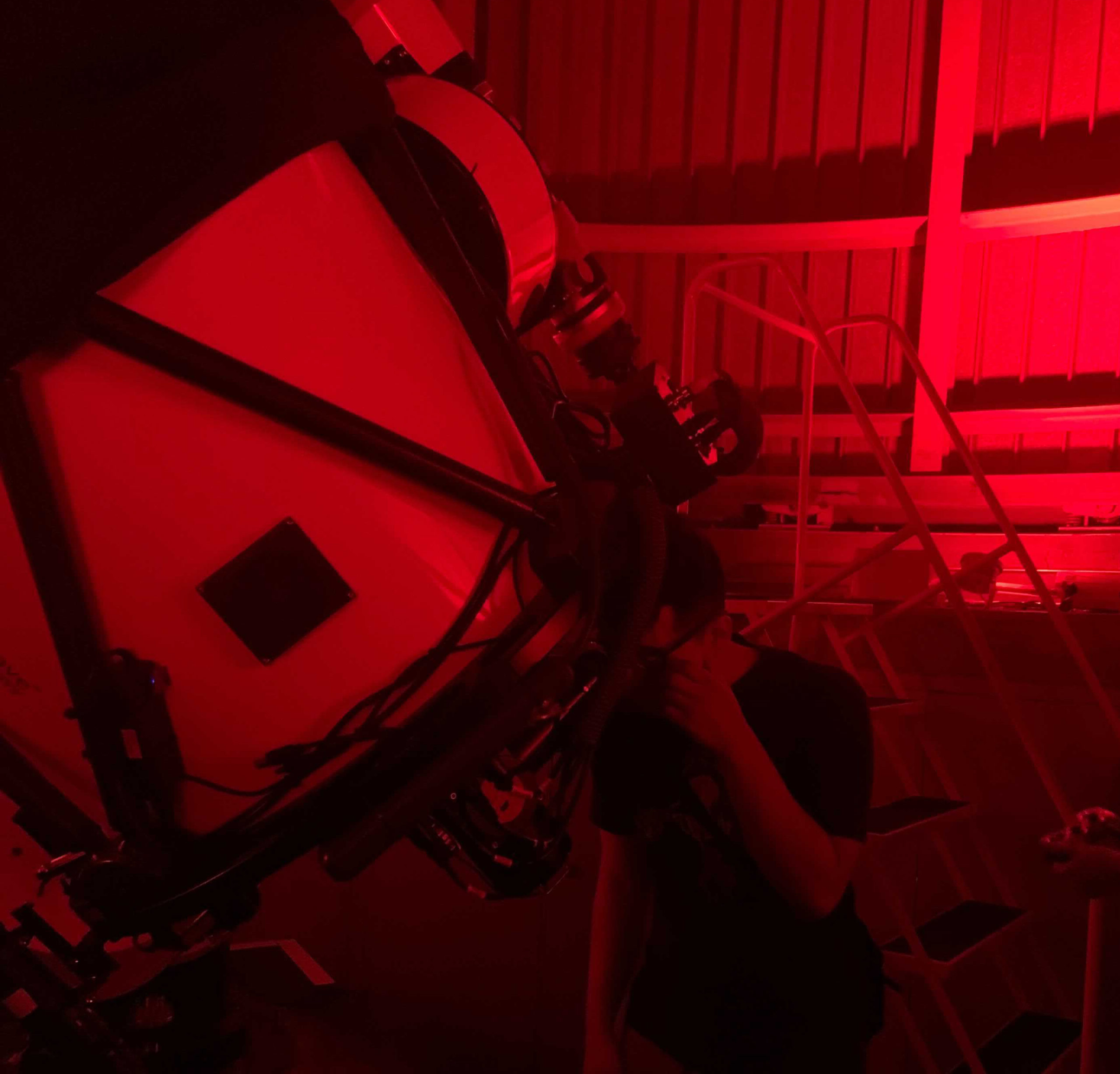 A person observing through a telescope in July 2021 at the 'Scopes at the Adler small-group experience inside the Adler Planetarium's Doane Observatory.
