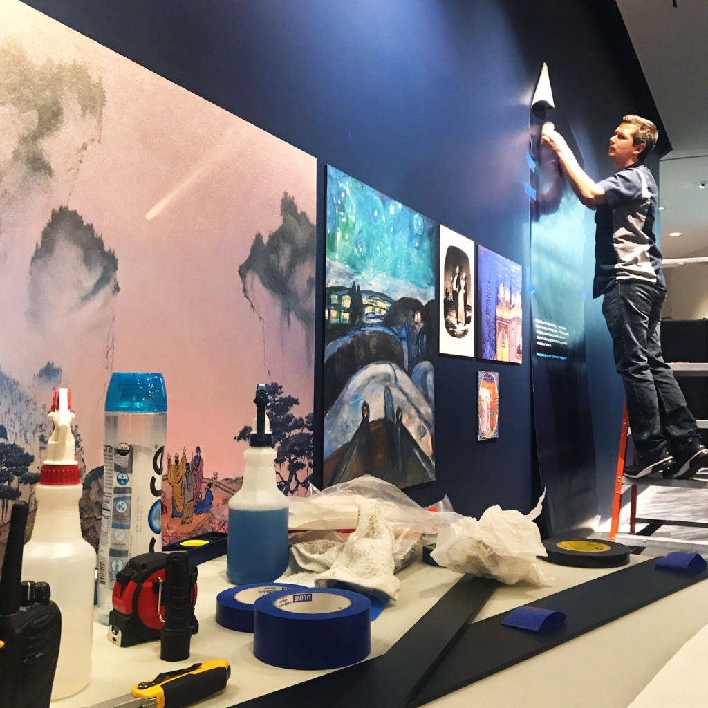 Neil Adam installing a graphic on a wall in The Adler Planetarium's new exhibit, Chicago's Night Sky.