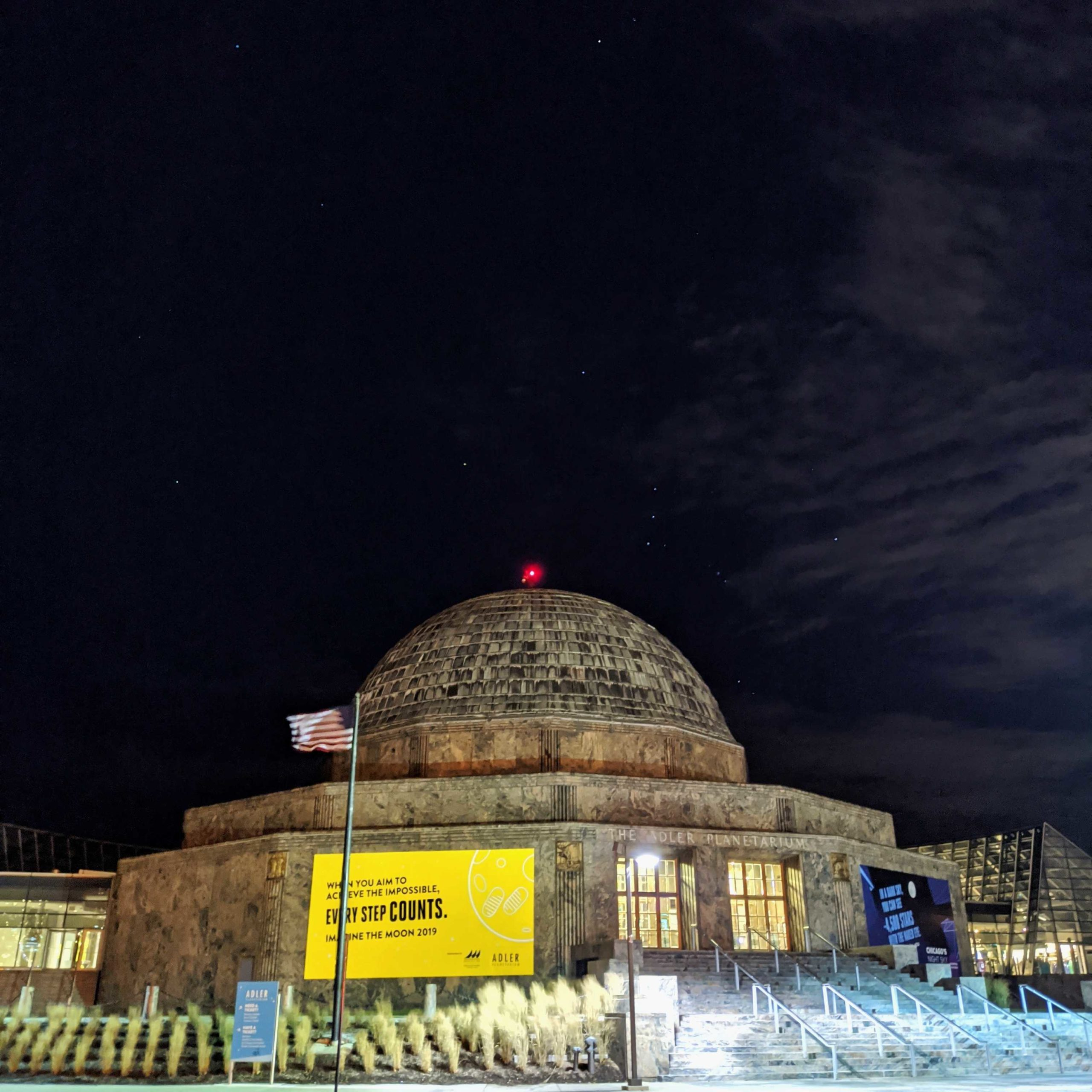 The Adler Planetarium at night with the constellation Orion shining in the sky.