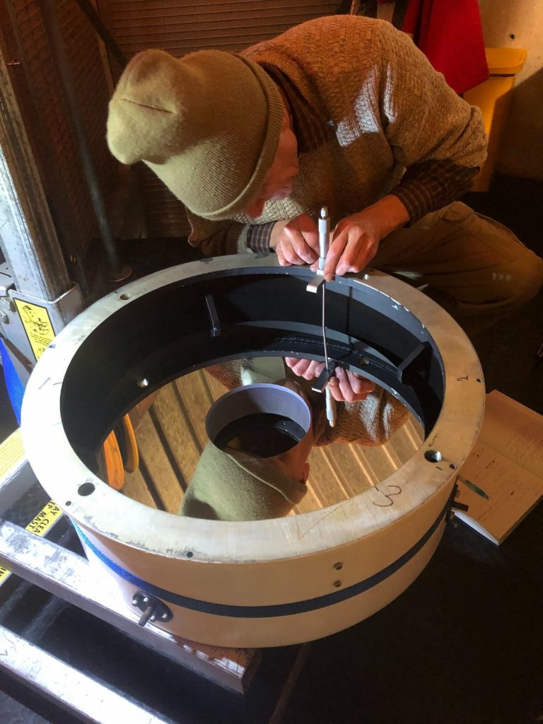 A volunteer from the Fox Valley Astronomical Society uses a micrometer to measure how level the edges of the telescope are.