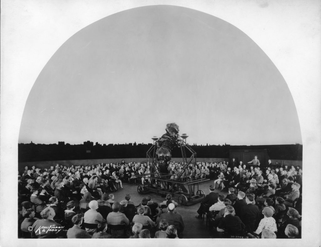 Image Caption: The Adler's first director, astronomer Philip Fox (standing up at the projector's control panel on the right) gets the audience ready for a demonstration with the Zeiss Mk II in the 1930s. Image Credit: Kaufmann & Fabry Co./Adler Planetarium Archives