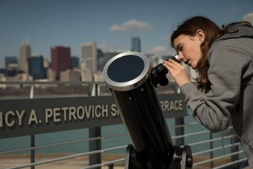 An image of a young girl telescope observing on the Adler's terrace.