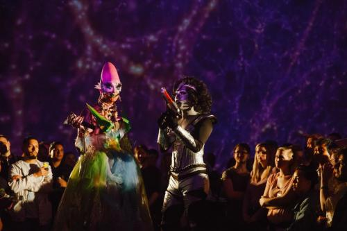 "Two drag queens dancing in the center of a crowd of people in the Adler's ""Grainger Sky Theater."""
