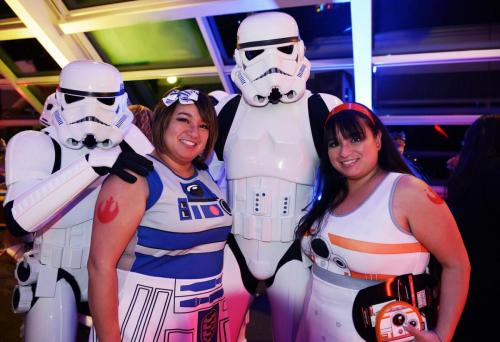 "An image of two ""Adler After Dark"" guests dressed in Star Wars cosplay, and posing with two stormtroopers."
