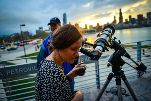 "An image of an Adler guest peering out of a telescope on the Adler's terrace during an ""Adler After Dark"" event."