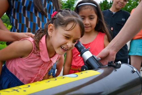 "An image of a young girl peering through a telescope during one of the Adler's ""Scopes in the City"" events."