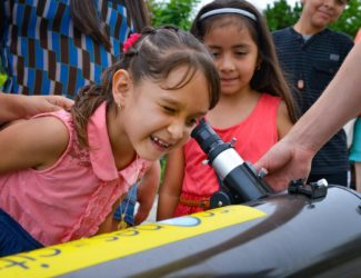 A little girl peers into a telescope at a 'Scopes in the City event.