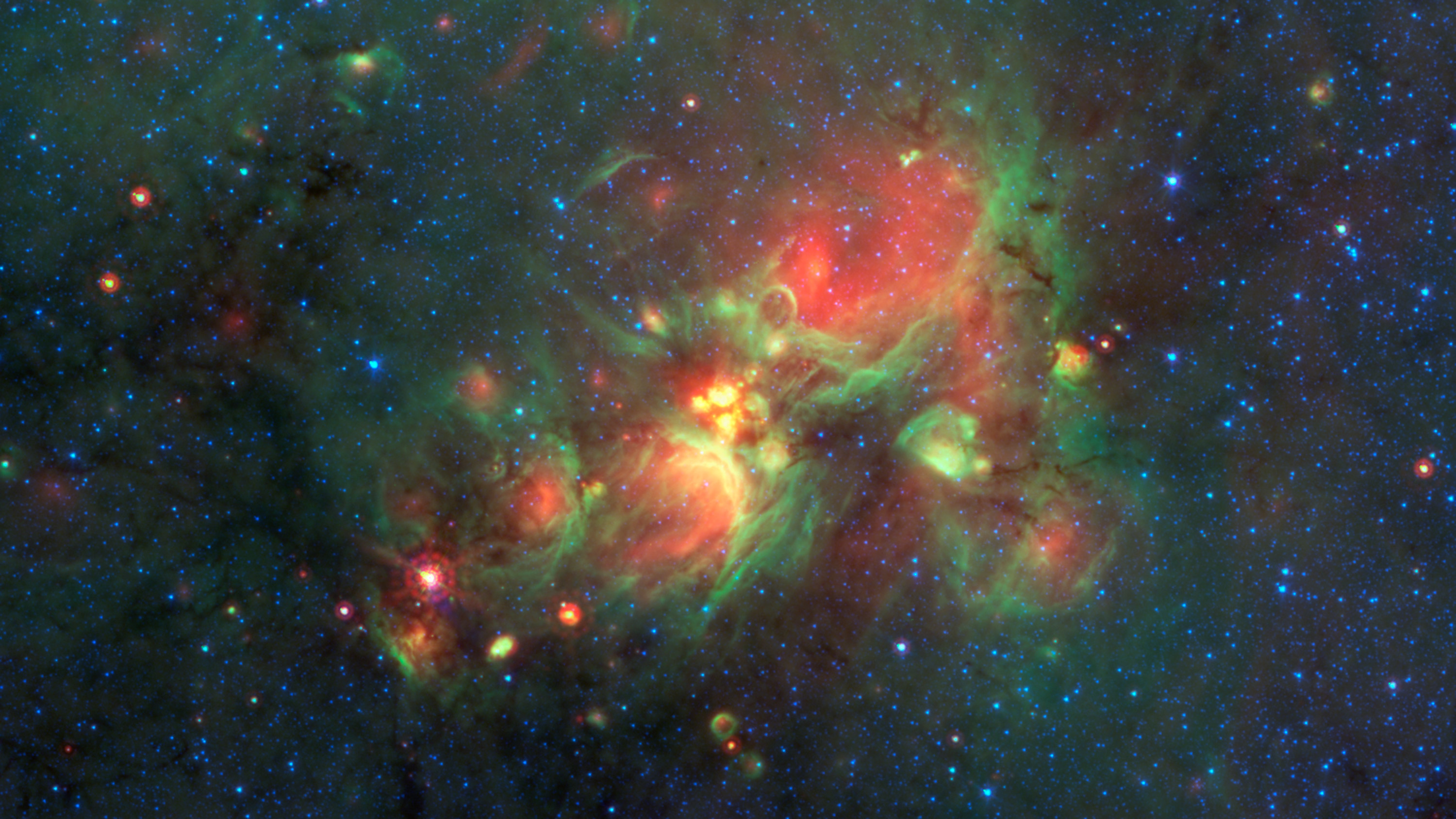 "Volunteers using the web-based Milky Way Project brought star-forming features nicknamed ""yellowballs"" to the attention of researchers, who later showed that they are a phase of massive star formation. The yellow balls -- which are several hundred to thousands times the size of our solar system -- are pictured here in the center of this image taken by NASA's Spitzer Space Telescope. Infrared light has been assigned different colors; yellow occurs where green and red overlap. The yellow balls represent an intermediary stage of massive star formation that takes place before massive stars carve out cavities in the surrounding gas and dust (seen as green-rimmed bubbles with red interiors in this image). Infrared light of 3.6 microns is blue; 8-micron light is green; and 24-micron light is red."