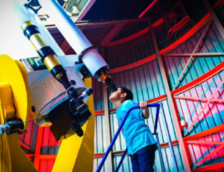 A young boy peers into a telescope in the Doane Observatory.
