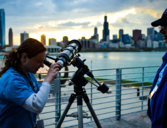 A guest looks out of a telescope towards the Chicago skyline on the Adler's terrace.