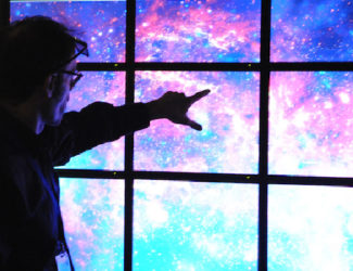 A guest points towards a video display of the cosmos.