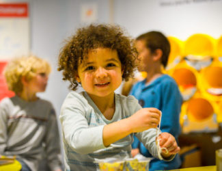 A young child smiling while working on a project in the community design lab.