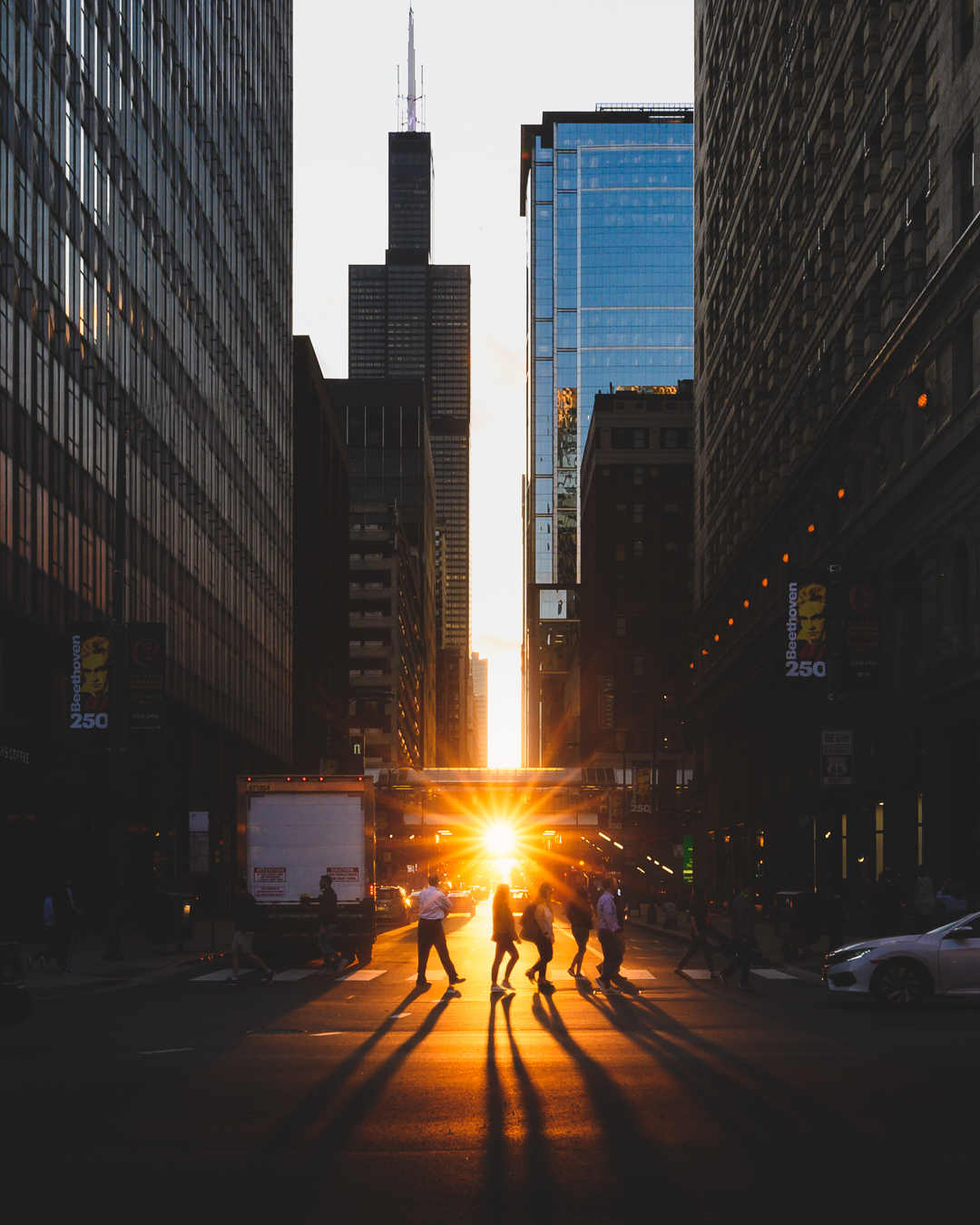 Pedestrians walking (during Chicagohenge) across a crosswalk while the Sun sets in the distance with the Willis Tower in view.